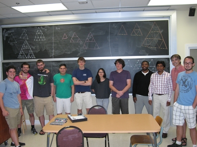 Undergraduate students standing in front of a blackboard