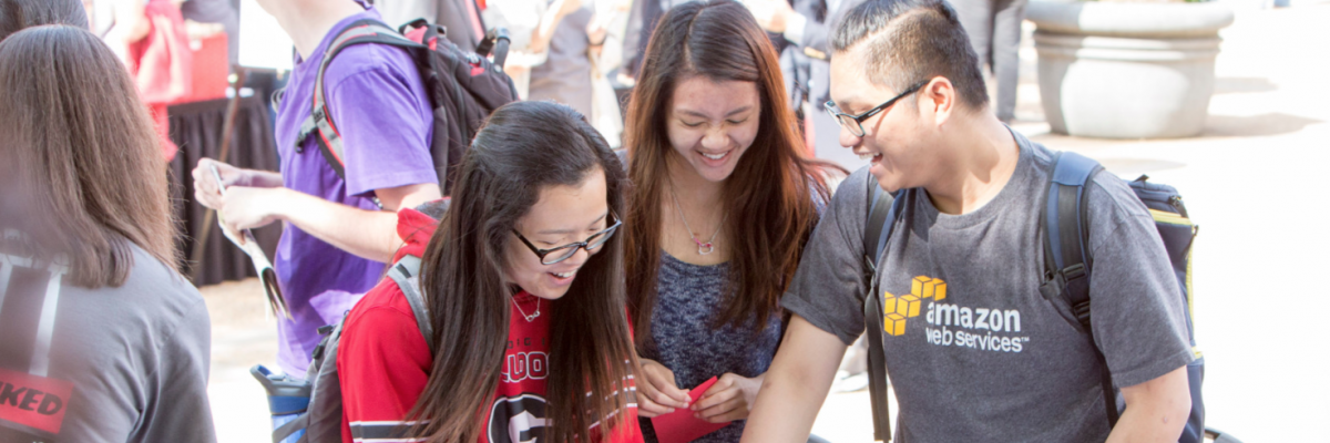 Minh Hoang, a freshman mathematics major from Vietnam and two other students, make a sign for a photo op on Donor Day